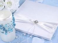 Svatební kniha s bílou stuhou a broží